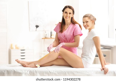 Woman having hair removal procedure on leg with sugaring paste in salon