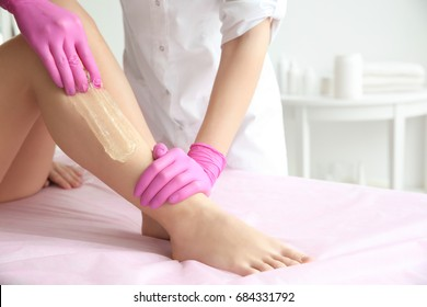 Woman having hair removal procedure on legs in salon. Depilation concept