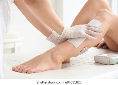 Woman having hair removal procedure on leg with wax depilatory in salon. Depilation concept