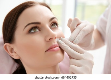Woman having hair removal procedure on face with wax depilatory in salon. Depilation concept