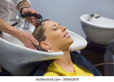 Woman having her head washed by hairdresser