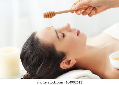 Woman having honey facial massage at spa salon