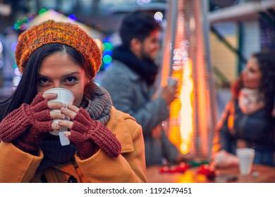 Woman Having Hot Drink Outdoors On Winter Market
