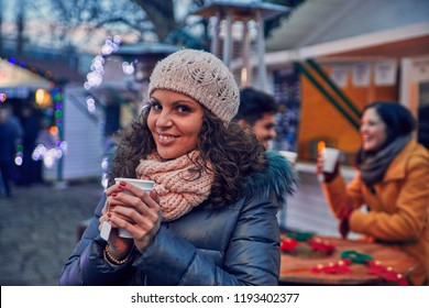 Woman Having Hot Drink Outdoors On Winter Market