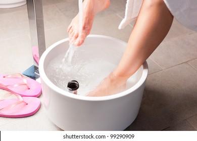 Woman having hydrotherapy water footbath in spa setting