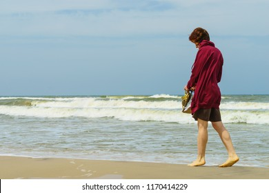 Woman having leisure time walking barefoot on beach during warm autumnal weather, shoes sandals in hand