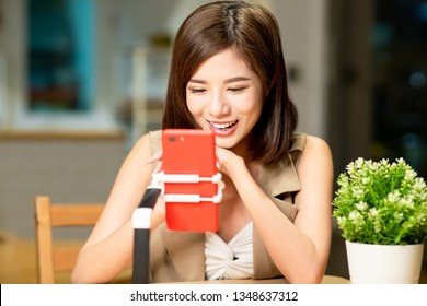 woman having live stream on cellphone at home