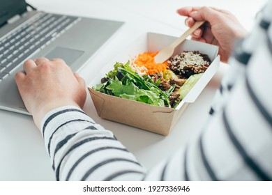 Woman having lunch from recycled bowl and using laptop. Concept of food delivery, quarantine, take out food