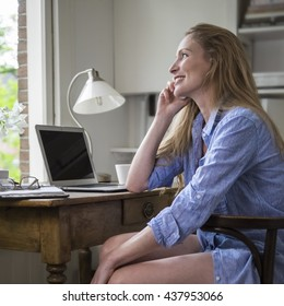 Woman having a morning phonecall in her home office