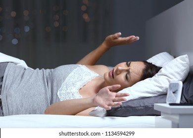 Woman having a nightmare lying on the bed in the night at home