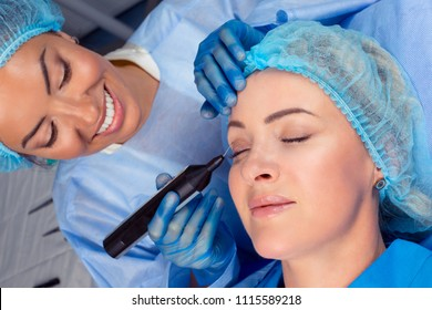 Woman having a non surgical procedure to remove eyelid skin excess with a laser device by a cosmetologist in a medical clinic. Thread lift procedure. Patient with eyes closed having lifting procedure
