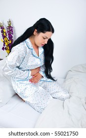 Woman having a painful stomach ache and sitting on bed with hands on abdomen