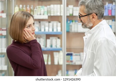 Woman having painful tooth ache, holding hand on mouth. Pharmacist helping and talking with customer, offering medicaments. Chemist wearing in glasses and white lab coat.