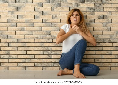 Woman having panic attack while sitting near brick wall