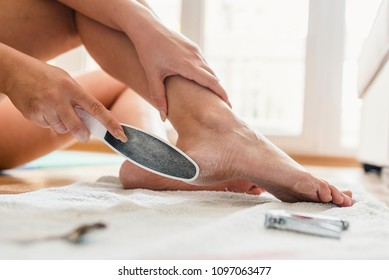 Woman having pedicure to her legs. Cares about woman's foot skin and nails. Woman Filing Foot. Female feet and callus remover tool. Treatment of feet and nails.