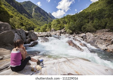Woman having picnic on beautiful mountain riverside in Switzerland, Verzasca Valley.