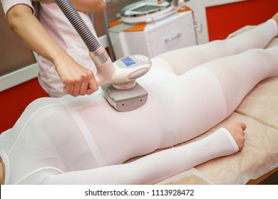 Woman having procedure of anti cellulite lpg treatment massage with therapist and apparatus in cosmetology clinic