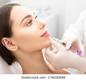 Woman having procedure lip augmentation. Syringe near womans mouth, injections for increase lips shape