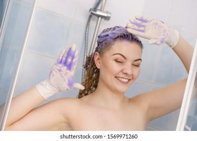 Woman having purple shampoo foam on her head under the shower. Female toning blonde hair using colored shampoo.