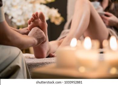 Woman having reflexology foot massage in wellness spa center