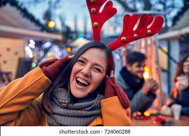 Woman Having Reindeer Horns On Her Head On Winter Market