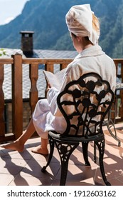 Woman having a relaxing summer day reading a book on a balcony with mountain views. Alone girl at a rural retreat and spa