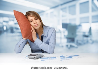 Woman having a rest (sleep, relax) in work. Burnout tired worker concept. Weary woman with pillow, graphs, sheets and calculator, office in background.