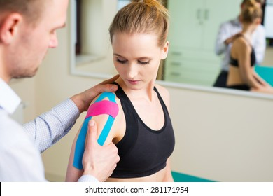Woman having shoulder physical therapy with kinesiotaping