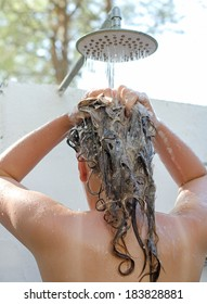 Woman having shower outdoors. View from the back.