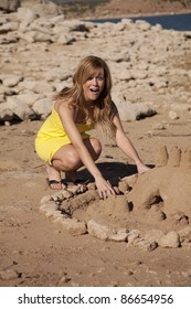 a woman having some fun building a huge sand castle.  She is shocked at how good it turned out.