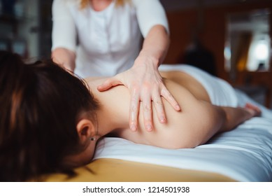 Woman having spa body massage treatment in the spa salon. concept of healthcare and female beauty. The masseuse makes a back massage with a massage oil close up