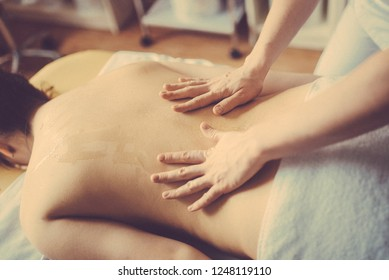 Woman having spa body massage treatment in the spa salon. Toned image. concept of healthcare and female beauty. The masseuse makes a back massage with a massage oil. back close up view