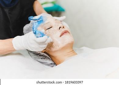 Woman having stimulating facial treatment at professional clinic - Shutterstock ID 1819603397