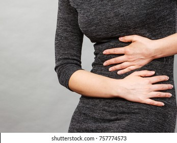 Woman having strong stomach ache. Syndroms of indigestion pregnancy. Female suffer on belly pain, holds hands on abdomen, part of body on grey