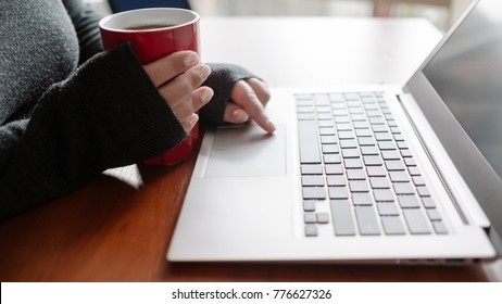 Woman having a tea and binge watching her favourite TV series on laptop. Movie download and video streaming