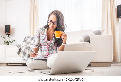 Woman having a tea, sitting on a floor in an apartment, writing down notes, opened laptop in front of her. Home office concept.
