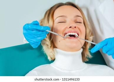 Woman having teeth examined at dentists . Doctor doing dental treatment