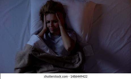 Woman having terrible headache lying in bed at night, strong migraine, top-view
