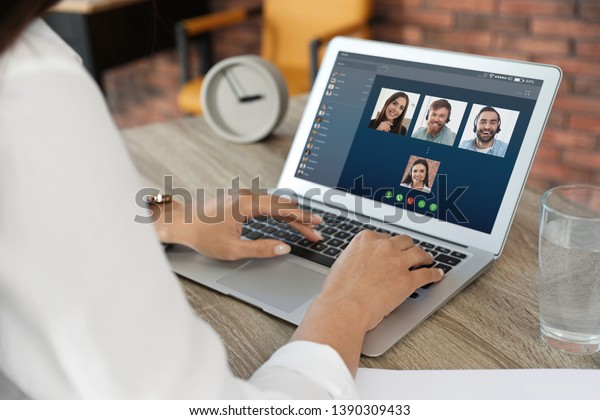 Woman having video chat with colleagues at table in office, closeup