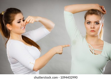 Woman having wet armpit her friend smelling stink being disgusted. Hyperhidrosis sweat, health social problem.