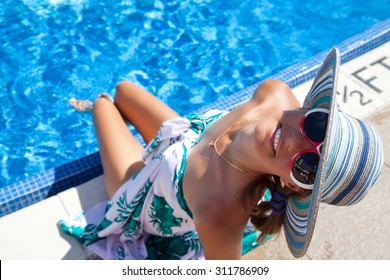 Woman in  hawaiian sarong relaxing at the luxury poolside, legs in a refreshing pool water. Girl at travel spa resort pool. Summer luxury vacation.