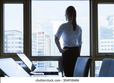 Woman in he office looking out the window.