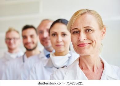 Woman as head nurse with team at clinic
