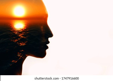 Woman head silhouette with sun inside with copy space. Multiple exposure image.