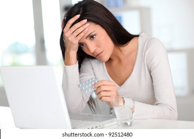 Woman with headache in front of laptop computer