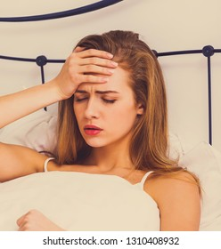 Woman with headache lying in bed. Hangover and young adult lifestyle.