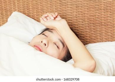 woman with headache lying on bed