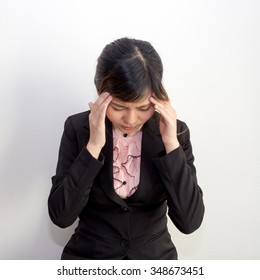 A woman with headache, migraine, stress, hangover in business executive dress, office syndrome concept