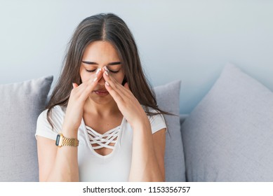 Woman with headache. Seasonal allergies and health problems. Sinus ache causing very paintful headache. Unhealthy woman in pain. Sharp strong sore. Flu cold or allergy symptom. Sinus pain, sinusitis.