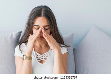 Woman with headache. Seasonal allergies and health problems. Sinus ache causing very paintful headache. Unhealthy woman in pain. Sharp strong sore. Flu cold or allergy symptom. Sinus pain, sinusitis.